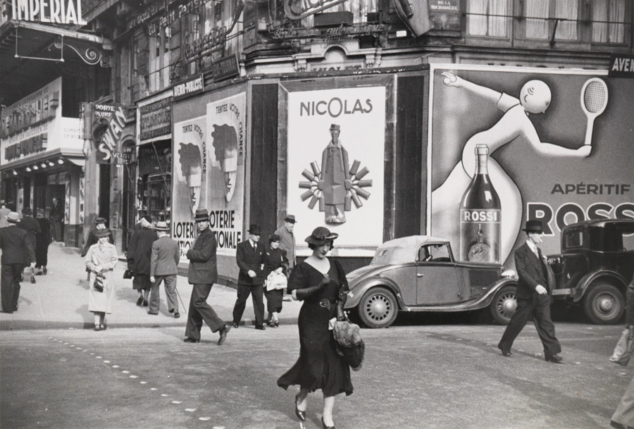 Parisians walk on the street past lottery and vermouth advertisements in 1935.Photograph by Maynard Owen Williams, National Geographic
