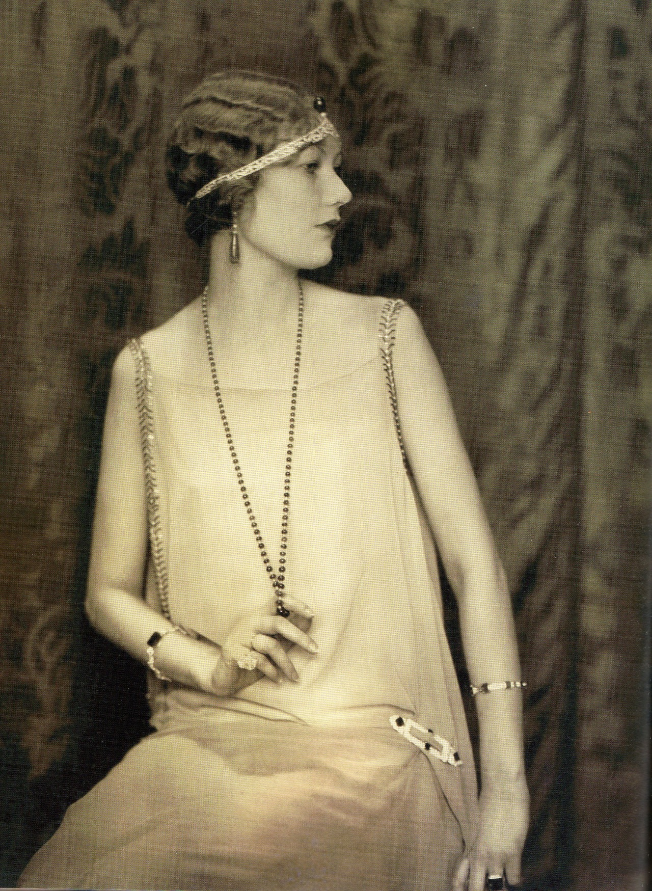 An introspective flapper in 1924 wearing a matching necklace and earrings of emeralds and pearls by Cartier. The dress pin and headband were also by Cartier. What is fascinating about vintage pins is what they were used for, not just to grace lapels but to accent belts, shoulders, sleeves and here, to highlight a graceful drape. Photo from Vintage Jewelry Design: Classics to Collect & Wear (Vintage Fashion Series) by Caroline Cox.