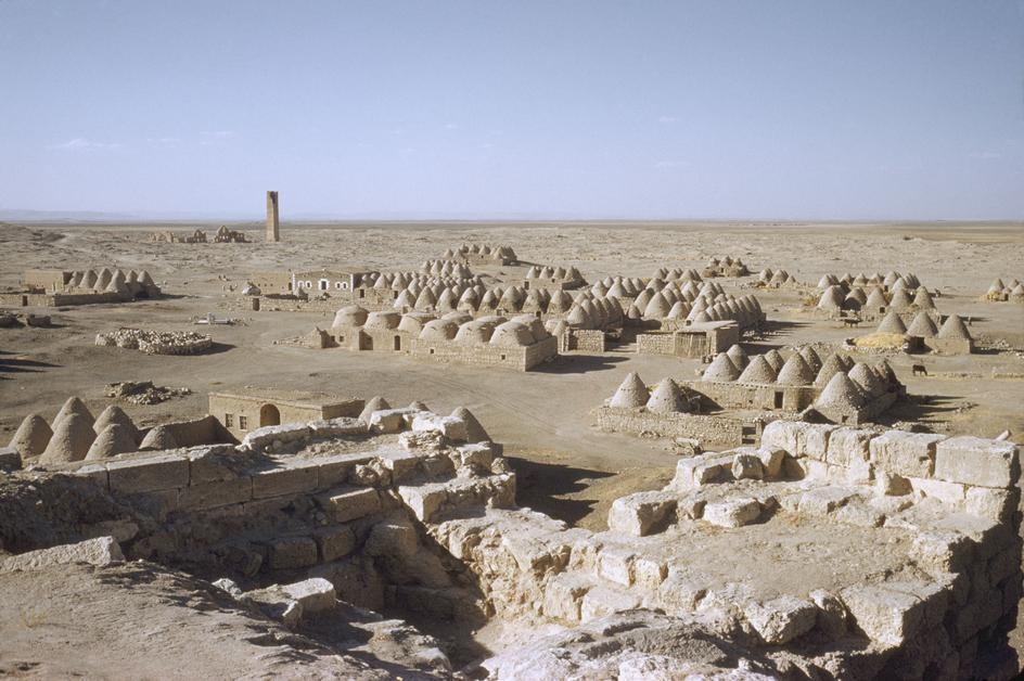 "fotojournalismus:  From ""Anatolian Civilisations"", 1983. Harran, the city was the chief home of the Mesopotamian moon god Sin, is famous for its traditional 'beehive' adobe houses, constructed entirely without wood. The design of these makes them cool inside and is thought to have been unchanged for at least 3,000 years. The tower on the horizon was an early observatory used for gazing at the galaxies and for worshipping the Moon God. [Credit : Ara Güler]"