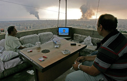 People watching television on balcony, with black smoke rising in background Beirut, Lebanon.