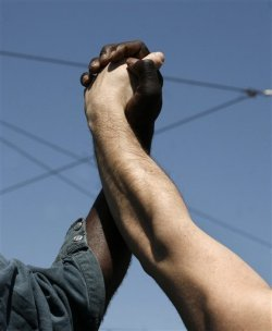 simply-war:  AP Photo - A Greek, right, and an immigrant worker march hand in hand in front of the Greek parliament in Athens on May 1, 2013. About 8,000 people took part in the subdued demonstrations as austerity-weary unions held a strike for May Day. The country's main labor unions are protesting soaring unemployment, which is the highest in the 27-country European Union, and the austerity measures the conservative-led government is enacting in return for crucial bailout loans.