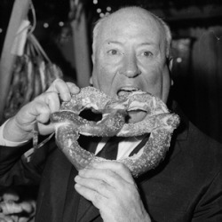 "vintageclassicscrapbook:  Alfred Hitchcock eating a giant pretzel on the set of ""Psycho""."