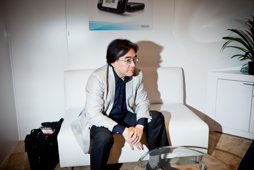 QUITE POSSIBLY THE GREATEST PICTURE EVER TAKEN OF SATORU IWATA It was announced earlier this week that Nintendo Global President Satoru Iwata would gain the additional title of CEO of Nintendo of America to fill the role that was left behind by Tatsumi Kimishima who was promoted to Nintendo Co., Ltd. Managing Director. The future of the company certainly looks… unpredictable, to say the least. Wii U sales have been severely lackluster thanks to a massive lack of worth caring about, and even 3DS sales have slowed down, but some could argue that it's probably because just about everyone who plays games already owns one by now (but that's almost definitely not the case). And so begins a new chapter for the company. Charting a course for the unclear voyage ahead. With E3 just around the corner, Sony's PS4 and the probable announcement of a new system from Microsoft will definitely give Nintendo and its president more than a few things to think about.  Much like the Marios and Donkey Kongs and Links and all the hundreds of Pokémon, Iwata is seen mostly by gamers as just another cutesy character in Nintendo's brand mythos. But then there's that picture of him sitting on a small white couch. The room, the luggage, the contemplative expression on his face - it's like something out of a men's lifestyle magazine. This isn't the same adorable Japanese man we normally see on stage at press conferences or wearing Luigi hats in Nintendo Direct videos. This picture shows a different side to the face of Nintendo - a Satoru Iwata rarely seen, and it's a safe bet that this is probably one of the closest glimpses we'll get at the real Iwata. Not the salesman on stage giving PR pitches to appease investors, not the precious little Nintendo Direct host reeling in consumers and fans, but the savvy businessman who has kept the company strong since he worked his way up from HAL Laboratory programmer in the 80's earned the title of President in 2002, making him the first president not related by blood or by marriage to the Yamauchi family who originally founded the company all the way back in 1889. When you think about all you can accomplish in a lifetime, you start to wonder what kind of legacy you'll be able to leave behind - how long your footprints will be embedded in history before being washed away by the tides of time. Just by looking at the picture above, it's clear that Satoru Iwata's legacy has just begun.