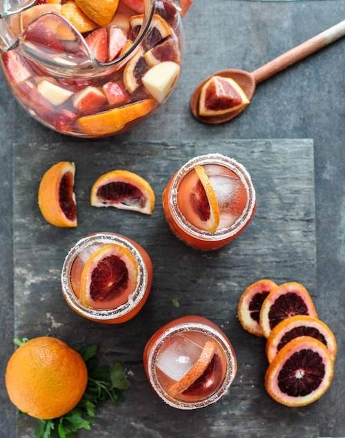 "Blood orange sangria by How Sweet It Is! Because you're worth it, and by ""it"" I mean ""day-drinking in the winter, everyone's been sick and overworked and cold, make yourself happy with the fanciest oranges and some delicious, delicious liquors."" Do you think this would work with regular oranges, too? Or is the beauty of the blood orange half the appeal?"