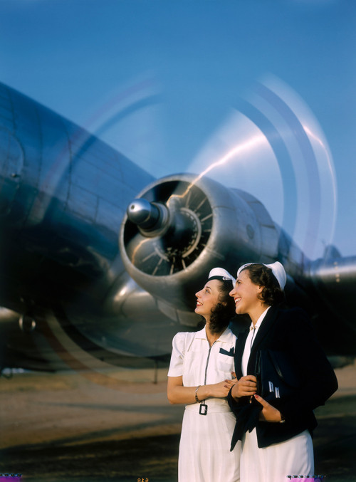 historicaltimes:  Two young women stand near a turning aircraft propeller, 1940