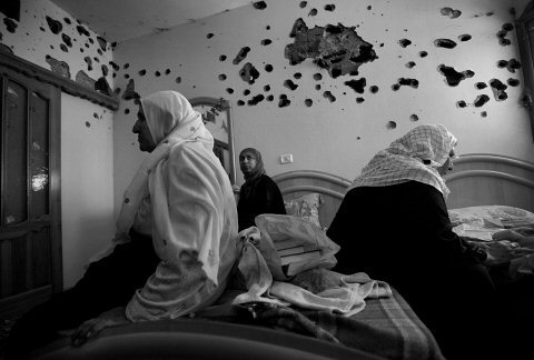 mediterraneum:  © David Guttenfelder Gaza- Members of the Palestinian el-Aljuwi family sit on their beds in a room that was riddled by Israeli gunfire in Beit Lahiya, northen Gaza Strip after two days of clashes in the area July 8, 2006.
