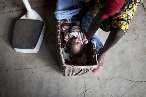 Photo: A woman and her child at the maternity unit in MSF's hospital in Nasir. The basket is the traditional way for Nuer mothers to carry their children. South Sudan 2012 © Brendan Bannon Different Kinds of HappyEmma Pedley is a British nurse working on community outreach projects with Doctors Without Borders/Médecins Sans Frontières (MSF) in Nasir, South Sudan. Read her MSF Field Blog here. Before I know it it's 5:00 pm and as I start to wearily gather all my things together into the Land Cruiser one of the consultants trots up to me to remind me about the baby still in the stabilization room. What baby? There have been dozens. The one you wanted to pass water. Oh, that baby. Not one but three hours have flown by since I first saw that child. As we rattle back over the uneven roads to the hospital I'm panicking internally and right now, with the tight band of headache pressing round my skull, I feel like I'm not thinking straight and my mind heads straight for worst-case scenarios. What if that kid does have concurrent malaria? Diagnostically the quick Parachecks aren't 100 percent infallible, but at MSF the microscopy blood films are … What if this drowsiness isn't just from dehydration, but from low blood sugars? What if the mother was right—what if that child really hasn't passed urine all night as well as all morning as well as all afternoon? What if he really didn't take any of that rehydration solution? What if I'd taken the other option and sent him straight to the ER? What if, what if, what if … ? Despite my training and qualifications I feel so, so unprepared for parts of this job sometimes—not so much professionally, but experientially, emotionally … unprepared for the heat … my heart feels leaden inside me and I'm barely holding back tears as I berate myself. We arrive at the compound and pull up outside the Emergency Room. Running around to the back of the Land Cruiser, I take the sleeping child from his mother's arms to carry him into the ER. As I unwind the blanket, the child rouses and starts crying—a weak, fitful cry that health care workers know and dread—the cry of a child with scant energy reserves left to cry with. The crying pauses … I pause … the startled black eyes below unblinkingly regard the worried brown ones above. A few heartbeats and a few hundred years pass … and suddenly the little man in my arms is crying—and I mean proper crying—a lusty, full-lunged bawling with all the might and main he can muster, and I feel like I've never heard a more beautiful sound in my life, because any child that can cry that hard is OK, not 100 percent OK, but OK nonetheless. My heart feels like it's going to burst with relief. And then there is a sudden warmth spreading across my lap and I jump up startled, still cradling the now half-naked yelling baby, watching the dampness seep across his trousers and mine and it's OK. He's passing urine, lots of urine—fantastic, amazing, brilliant amounts of wonderful urine that I've scared out of him that tell me that the kidneys are working perfectly, and the urine is streaming down my arms and legs and puddling at my feet and the baby is crying and the mother is clucking and fretting at the urine on me and I'm laughing because I'm so relieved, and I'm laughing so hard because who knew a crying baby peeing all down me could make me so, so happy? And then without knowing quite why I'm crying too and my heart is bursting wide open, and all the stress is pouring out and there are tears pouring down my cheeks and the urine is still pouring down my arms and they all mean the same thing—the baby is OK, I'm OK, everything is going to be OK.