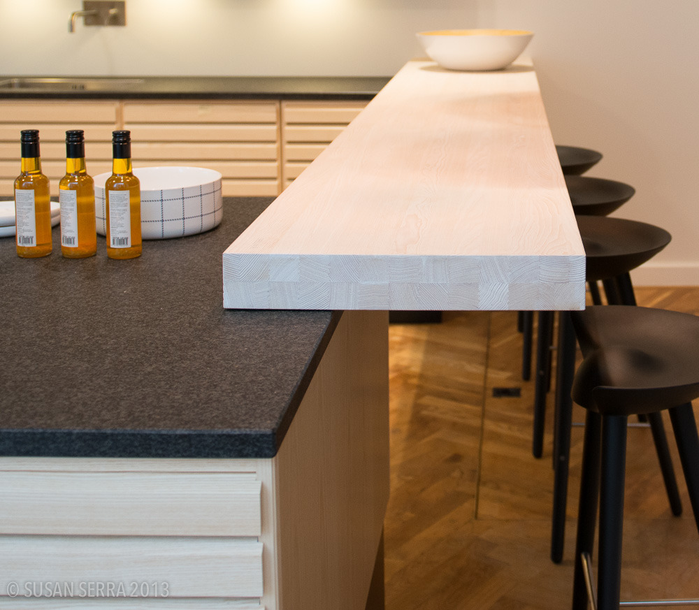 A current look in European kitchen design are layers of countertops, one type of surface set on top of another for different reasons such as special prep areas, dining or for an aesthetic purpose.