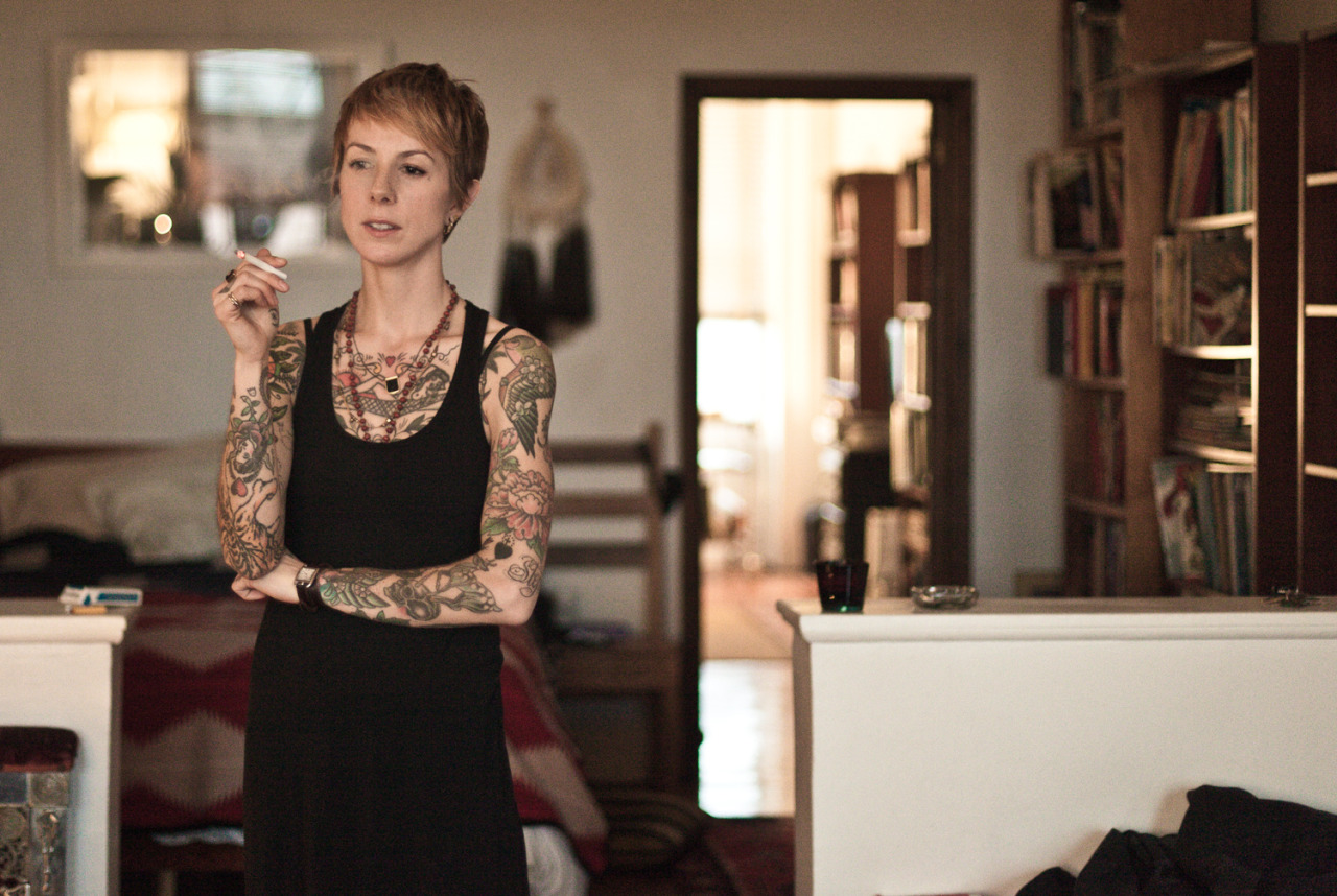 "The Creators of NYC: Tattoo Artist Virginia Elwood Josh Wool spent a decade as an executive chef, opening restaurants across the south. But all that changed in 2010, when the carpal tunnel in his hands meant he could no longer work. To keep from going stir crazy, he picked up a camera and found his next calling. Two years, thousands of portraits, and a move to New York later, Wool is documenting the people who inspire him on a daily basis. Welcome to Creators of NYC. Virginia Elwood Tattoo artist Virginia Elwood has been plying her craft for the last 12 years and has made a name for herself at New York Adorned as one of the top talents in the industry. I first saw her work several years ago, and I bumped into her on the G train in Brooklyn shortly after I arrived in New York. After almost a year of exchanging emails, we finally sat down in her Carrol Gardens home. When did you figure out that tattoo art could be an actual career? When I was a little kid, I remember wanting to be either a scientist, a ballerina, or a garbage man. I don't think I had a definition or reference for ""art as a career."" I set out on my own at a really young age and drifted from one random job to the next … a career in fine arts was not a realistic or practical goal at that time. The idea that a person could actually get paid to draw didn't occur to me until I fell head over heals for tattoos as a teenager in the 90s.   Which came first, drawing or tattooing?  I was always drawing and making shit as a kid, but I have very little formal training in art. It might be more fair to say that I have none! Everything I've learned about drawing, composition, color theory, et cetera comes from working with really talented and generous tattoo artists over the years.  Stylistically, is there a big difference in mediums for you? I think of tattooing mostly (but not exclusively) as a craft. An incredibly creative, sustaining and inspiring — but extremely strict — craft. And by that I mean it's possible and necessary to apply your own creative sensibility to your tattoo work, but you should never sacrifice the fundamentals of good tattooing to accomplish your own, or your clients', weird artsy goals. Someone has to wear your experiment for the rest of their life.  Has living in New York affected your work as an artist? I don't think you could live in New York City and not have your work be affected. On one end of the spectrum, you may be overwhelmingly crippled by the fact that you'll never ever be as [insert adjective of your choice] as [insert person of your choice]. On the other end, you might be equally as crippled by the heart-wrenching beauty of all that creativity. Most days I aim to wake up somewhere in the middle so that I can actually function. The tattoo world has come into the limelight in recent years. Is that a double edged sword? I got into tattooing on the tail end of the pre-internet days, and even though it wasn't that long ago, it was really different. Tattooing was, is, and always will be fucking awesome regardless of what the current mainstream trends are. It feels a bit wrong for me to talk about tattooing's past (even it's most recent past) and future because I'm still dumbstruck that I get to have this job. I just have too much respect for the tattooers who came before me to pretend as if I'm qualified to speak of days past. I feel lucky they even let me in the club. What's a normal day for you entail? Coffee, dog, draw, draw, draw, more coffee, draw, email, emails, bike ride, tattoo, tattoo tattoo, food, more dog, maybe more coffee, draw, paint, write, read … with some eatin' and lovin' thrown in the mix. — Photos and text by Josh Wool"
