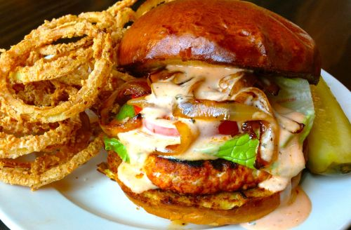 This Burger of the Week is going to melt your face off with it's flames…The Chicken Sriracha Burger aka The Firebird! Grilled chicken burger marinated in sriracha & chili spices, topped with lettuce, tomato, sautéed onion & sriracha aioli on a LeBus brioche roll.  Served with sriracha battered onion rings, aka Fire Rings,  and a spicy pickle spear.   Available right now for a limited time.