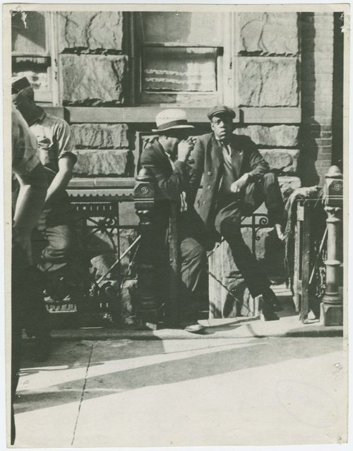 "Was one of Brooklyn's finest in Harlem in 1939? This Sid Grossman photo of ""Harlem Loiterers"" from the Prints Collection at NYPL's Schomburg Center for Research In Black Culture has created quite a stir since being posted to the Center's Facebook page the other day. Why? Because the man on the right looks a heck of a lot like Jay-Z (for evidence, check out these photos of Jay-Z when he visited The New York Public Library in 2010). Cue Twilight Zone music, right? Schomburg's Curator of Digital Collections Sylviane A. Diouf found the photo while researching an exhibition, and said, ""I was immediately struck by the similarity to Jay-Z and actually laughed out loud … I still hope somebody will tell us who that young man really was."" So is Jay-Z a time traveler? Is this someone else - anyone know who? What do you think?"
