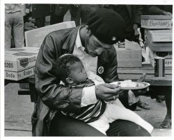 "holyshithistory:  A Black Panther feeds his son at the ""Free Huey"" rally in Oakland, California. February 17, 1968."