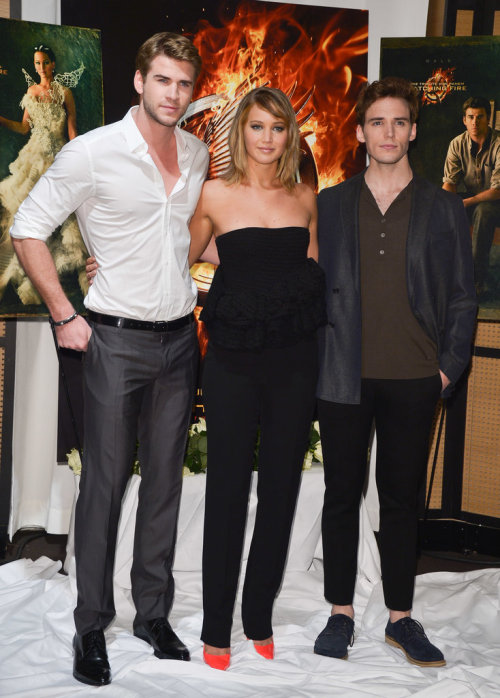 Jennifer Lawrence and Liam Hemsworth linked up with their Catching Fire costar Sam Claflin this morning for a photo call at the extremely rainy Cannes Film Festival!