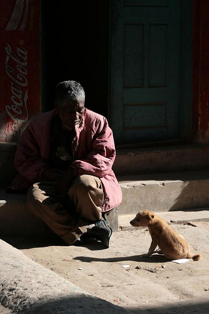 quietbystander:  untitled by MattTownsend on Flickr. A street dog sits for a moment next to a man begging on a corner of Boudhanath, Nepal.