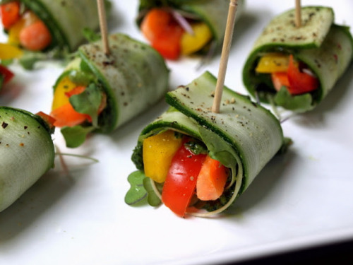 Raw Zucchini Wraps with Kale Pesto     What you'll need      1 - 3 zucchini, thinly sliced lengthwise*     red bell pepper, julienned     yellow bell pepper, julienned     carrots, julienned (I used baby carrots, cut into quarters)     sprouts/micro greens of choice     cilantro, optional     fresh cracked pepper     tooth picks     Kale Pesto      1 cup basil or kale     1 cup kale     1 clove garlic     2 tablespoons tahini, optional     3 tablespoons or so extra virgin olive oil (if not using tahini add 1 or 2 extra tablespoons olive oil)     himalayan salt to taste      Amounts here will vary on how many your making, use your best judgement on how much you will need. If you can't find sprouts or micro greens, try using cilantro or fresh basil leaves.       For the kale pesto, place ingredients into food processor and process until desired consistency. Taste for seasoning.       Lay your zucchini flat on a hard surface, layer with the pesto, add sprouts, veggies and starting from the veggie end, roll and stick with a toothpick in the center. Top with cracked pepper. Serve and enjoy!      * Look for the smaller zucchini, they will be the perfect size for these bite size rolls. The length and width is just right.