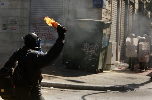 A hooded youth throws a petrol bomb at riot policemen in Athens' Syntagma square during a 24-hour labour strike September 26, 2012. Greek police fired teargas at hooded youths hurling petrol bombs and stones as tens of thousands took to the streets in Greece's biggest anti-austerity demonstration in months on Wednesday. REUTERS/Yannis Behrakis