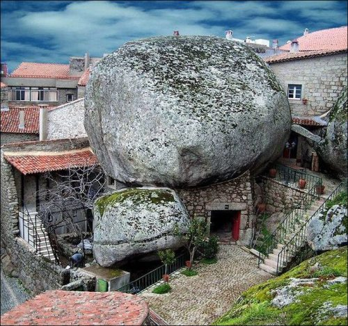 earth-phenomenon:  Southeast of Serra da Estrela in Portugal, perched on the side of a mountain, is a lonely and enchanting village of Monsanto. The village is built among rocks, with houses squeezed between gigantic boulders, and tiny streets carved through the rocks. Monsanto's appearance hasn't changed in centuries. Some of the granite houses have Manueline doorways and the ruins of a castle that started as a Lusitanian fortified settlement, affords magnificent views stretching as far as Serra da Estrela.