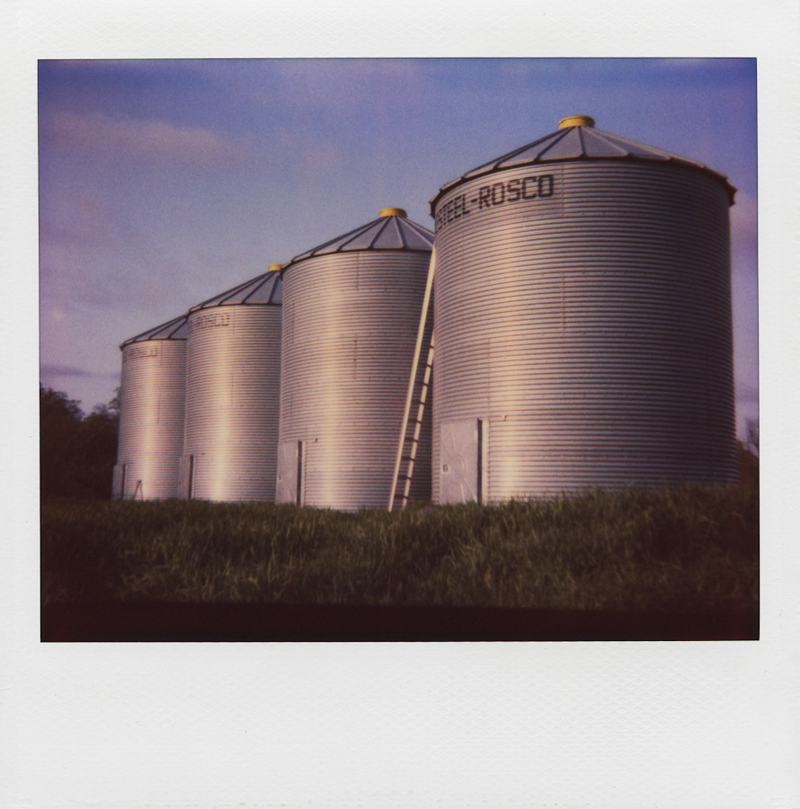 These are four steel grain bins and a ladder.