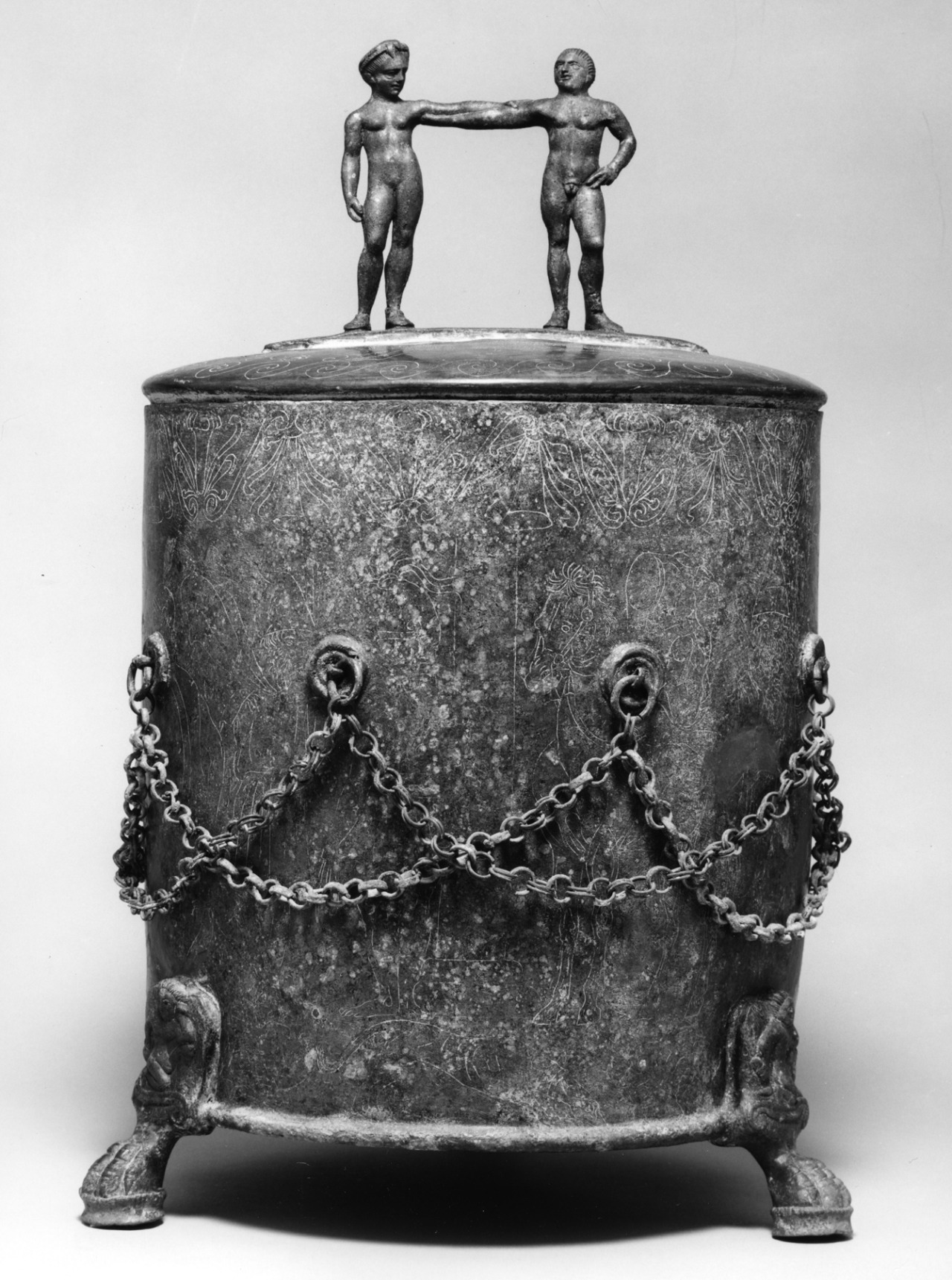 Etruscan Cista Depicting an Assembly of Warriors, 4th century BC, made of bronze. Artifact statement from the Walters Art Museum:  Cistae were containers used to safeguard precious objects, including mirrors, perfume flasks, and cosmetics. A particular type of cista was made during the 4th and 3rd centuries BC in Praeneste, a site in Latium (the region around Rome) that was heavily influenced by Etruscan culture. The elaborately engraved scenes are thought to imitate famous, but now lost, Greek wall-paintings. The ancient metalworker often pressed a white substance into the engraved lines in order to accentuate the decoration. The handles commonly take the form of human figures. Many artists in other early Italian cultures similarly incorporated figures of humans in functional objects. A scene of warriors assembled within a large palace or hall is a common decoration on cistae. On the front, at left are two running figures carrying shields; an eagle flies over the left figure. Three helmeted warriors appear to the right. On the back is a seated young man, his armor gathered around him and a horse at ready nearby. A satyr and a maenad with their arms intertwined form the lid's handle. The vessel's feet have the four toes of a lion but are shaped like a bird's claws; each is topped by winged youth.  Courtesy & currently located at the Walters Art Museum, USA