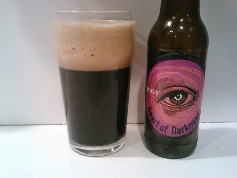 #512: Heart of Darkness – Magic Hat Brewing Company, South Burlington, Vermont Another stout today. What can I say, I've been in the mood for them and my 'fridge has been stocked with them via happenstance. I've got to drink them sooner or later, and they're often the perfect companion after working a 10-hour shift and getting home at 3:00 AM. This one was kindly donated to me by Scotches. It's brewed with brewed with Pale, Crystal, Roasted Barley, Chocolate, and Munich malts, and hopped with Apollo and Goldings. Checks in at 5.7% ABV. Pours with a towering, massive, creamy mocha-colored head, capping an opaque, inky black body. On the nose, chocolate. Chocolate in every which way. Milk chocolate, semi-sweet chocolate, bittersweet chocolate, it's all there and accounted for. A bit one-dimensional on the nose, but hey, it's hard for me to criticize a beer for smelling of chocolate. On the palate, I'd say the aroma's promise is kept pretty well, as it's indeed wall-to-wall chocolate, but the winner here is the mouthfeel. Creamy, rich, nourishing, it absolutely enrobes the tongue and provides the perfect pedestal for the rich chocolatey malt flavors. Bit of a caramelly butterscotch thing there, too. Finishes mostly sweet, with a fleeting bitterness. The Verdict: The curmudgeon in me would say that this beer would benefit from more of burnt, roasted edge to take off a bit of that sweetness, but ah, whatever. This beer is an irresistible sweet treat. Get over it.