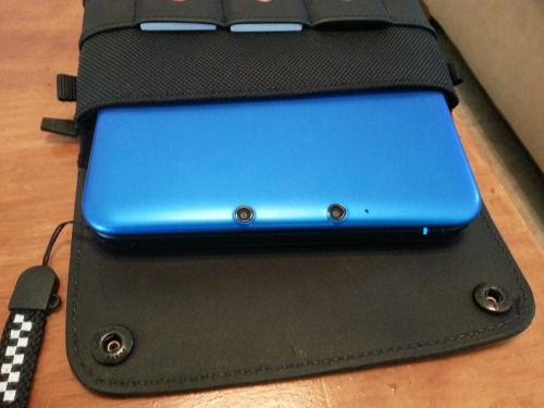 Waterfield 3DS XL CitySlicker Case Review -  I've owned my 3DS XL since day one, and it travels everywhere with me. Unfortunately there are virtually no decent cases for it, and the ones out there are just re-purposed DSi XL cases. I stumbled across Waterfield's 3DS XL CitySlicker case online, and deliberated over the purchase for quite some time. Fifty dollars is no small sum, and the shipping is hefty as well. Not to mention the fact that the video showing off the case on their website is for the old case that fit the original 3DS. Needless to say, I was wary, but tax return season rolled around and I took the plunge.     After a few days and some emails with their support team telling me the case was, in fact, out of stock, I received my black on black, leather bound, hand-stitched 3DS XL case. The first thing that stuck out to me was the awesome YKK zipper on the stretchy nylon pouch that spans the back of the case. It felt rugged and, as goofy as it sounds, it zips really nicely. The pouch itself can be stuffed full of things since it stretches, but too much makes the case a hassle to hold and fit in bags. I'm actually able to fit my entire phone in there, case and all, with little trouble.     The flap on the front of the case is held on by two snaps that keep it in place, and it covers three game compartments. While I doubt the system would come sliding out anytime soon, I'm nervous about the games getting loose and falling out of the flap, but so far they've stayed snugly in place. The system itself fits into the pouch nicely, and it's lined with a soft material meant to prevent scratching. My only complaint about the pouch is that the bottom of it has no padding other than the nylon, and since my strap means I put the system in hinge down a high enough drop could likely cause some real damage. Of course, this could be prevented by putting the other edge of the system down, but if you're like me and refuse to remove your Mario Kart DS strap from 2005 then you'll that I can't remove it.    To help with removal of the system there's a handy-dandy loop to put your finger in for leverage. This might seem insignificant, but anyone who has owned enough handhelds can tell you that more systems are dropped removing them from protective cases than any of us like to admit. Both sides also have small loops probably meant for clips or hooks, you know, in case you want to clip it to your belt while you go skydiving or rock climbing or whatever.    Overall, if there were a multitude of cases available for the 3DS XL, I might tell you that, while very nice, this case doesn't warrant the almost sixty dollars after shipping that I had to pay for it. As it stands, this seems to be the very best case available for a system that isn't spawning a lot of accessories, and for now you're going to be hard-pressed to find anything that even comes close. It has been thoughtfully designed, and I've had very minimal complaints with it thus far. The lack of padding on the bottom and worrisome game slots are my only real concerns, and only time will tell if either of them becomes a real problem. The case can be purchased here.