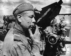 Soviet gunner resting by his 122 mm Howitzer after a battle with German tanks near Kaunas.