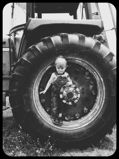 I remember playing in the same tire wheel as a child. Funny how the 4430 continues to inspire play & curiosity.   As we drove the tractor around I noticed how the grass - clovers, buttercups, dandelions and cow pies — were just like how I remember them as a kid.  When I showed my wife this picture, at first glance, she thought I'd found a picture of myself at the same age as our son on the farm  — in some ways, I think I did.