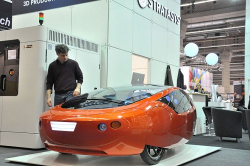 "Meet the Urbee, an incredibly lightweight 3D printed car.  Kor used the design freedom of 3-D printing to combine a typical car's multitude of parts into simple unibody shapes. For example, when he prints the car's dashboard, he'll make it with the ducts already attached without the need for joints and connecting parts. What would be dozens of pieces of plastic and metal end up being one piece of 3-D printed plastic. ""The thesis we're following is to take small parts from a big car and make them single large pieces,"" Kor says. By using one piece instead of many, the car loses weight and gets reduced rolling resistance, and with fewer spaces between parts, the Urbee ends up being exceptionally aerodynamic."" How aerodynamic? The Urbee 2′s teardrop shape gives it just a 0.15 coefficient of drag.  From the pictures, it appears to have only three wheels, so I think 'enclosed coffin-trike' might outshine 'car' as a descriptor.   Via Wired"