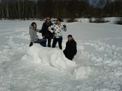 Building a praying snow woman on frozen river.
