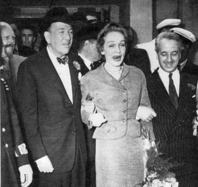 Noel Coward and Major Donald Neville-Willing welcome Marlene Dietrich to London for a season's performances at the Cafe de Paris. (c. 1955)