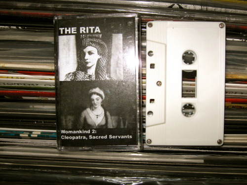 "The Rita - ""Womankind 2: Cleopatra, Sacred Servents"" (Survivalist Deathcamp 2012) So I'm listening to this new Rita jam and one of my peeps walks in and is like ""Yo, what's this shit? Your stereo broken bro?"" And I'm all like ""Nah dawg, it's a new joint from The Rita!""   He's like, ""what the fuck IS it?"" ""Harsh noise wall! Sam Mckinley takes a sound source and manipulates and distorts it to the point that it's an unrecognizable wall of noise! It's very meditative and deep! I love it!"" Then he shot me a look like I'M the crazy one. Whatever! One can only roll their eyes at such stupidity. -Log. PS: this probably didn't actually happen."