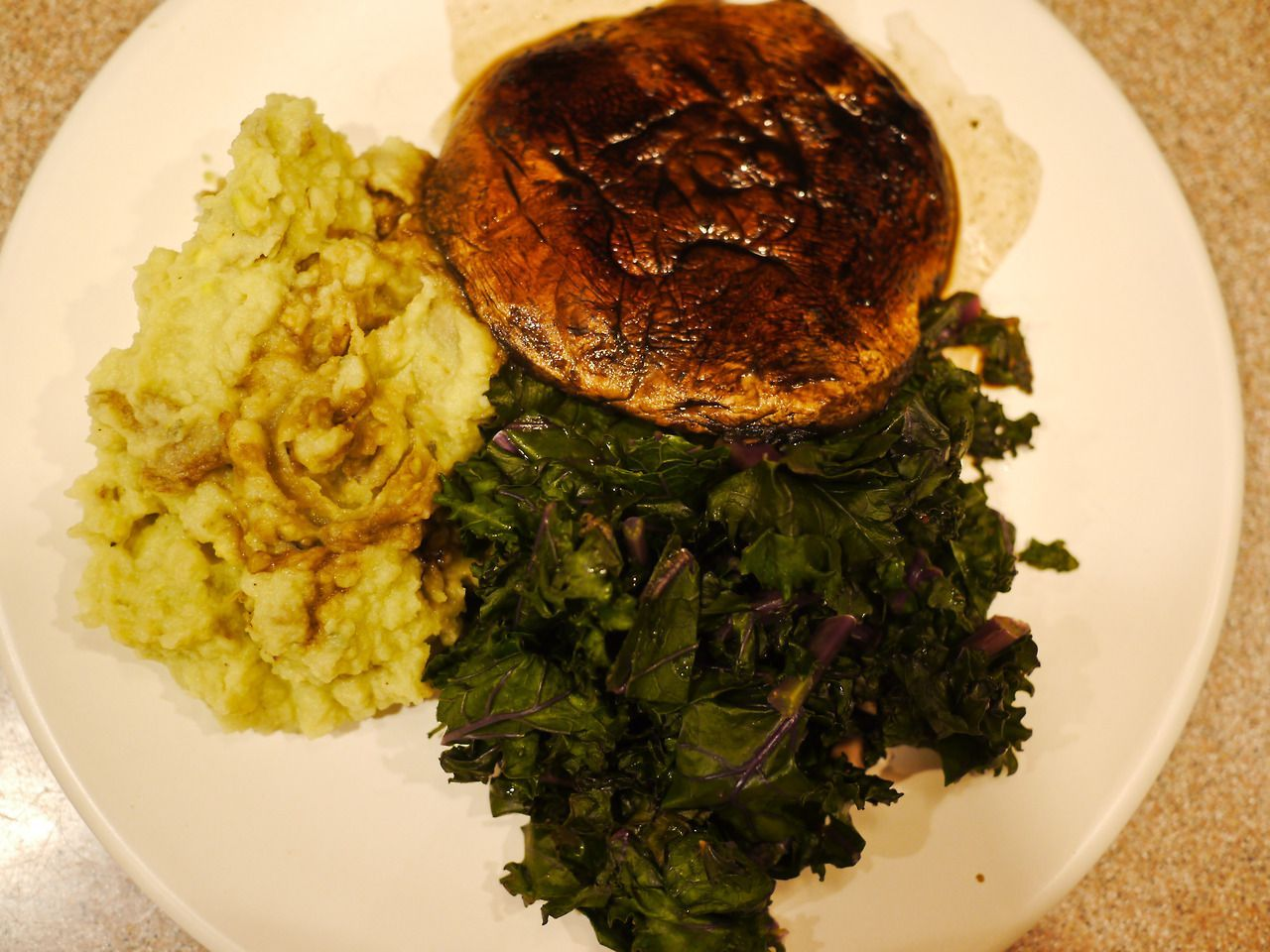 Portobello Steaks with Red Kale and Avocado Mashed Potatoes  Quarter about 1.5lbs of potatoes. Boil over high heat for about 15 - 20 minutes. Drain and put potatoes back in pot. Add 1/2 cup non dairy milk, 1 tbls non dairy butter, 1 sliced avocado, 4 cloves garlic, and salt and pepper to taste. Mash and smooth together until your mouth waters.   Make a marinade for the portobello steaks with 1 tbls veggie broth, 1 tsp rice vinegar, 2 tsp soy sauce, 1/8 tsp red pepper flake, and a dash of chili garlic sauce or cayenne. Brush mushrooms on bottom with marinade. Place over a hot hot skillet and then coat the top of the shroom with the marinade. Let them grill for about 4 minutes on each side, adding marinade as needed.   Chop a bunch of red kale and add it to a skillet with 2 tbls veggie broth, 1 tbls mustard, and 2 tsp white wine vinegar. Incorporate, cover, and let simmer for about 4 minutes, probably a little less. Just enough to wilt and soak up flavor.   Plate it and drool!