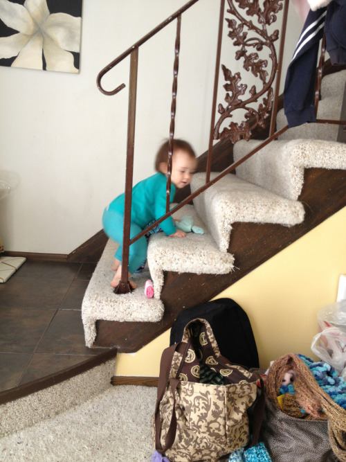 Bringing her clothes from her diaper bag upstairs.