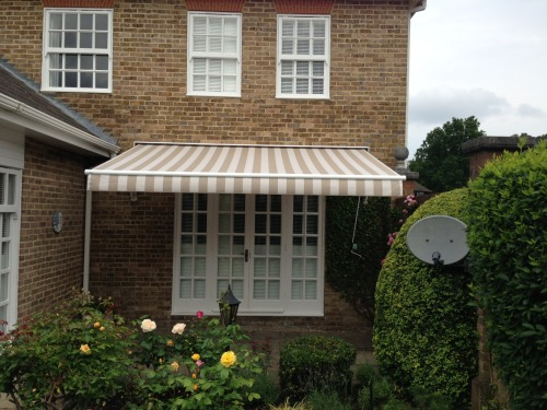 One manually operated folding arm awning covered in acrylic material.