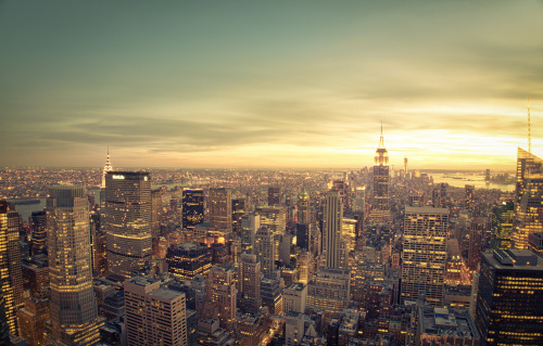 "New York City. Skyline cityscape at sunset. There is something really extraordinary about the shift between day and night in New York City. It's gradual and at the same time abrupt in its magnitude. The lights on the skyscrapers flicker on as the night sky pulls itself over the city while the sun is still dancing with the horizon. I love this time more than I love the moments when the sun disappears for the night. It's this sort of in-between time that seems to suit a city full of people who feed off the frenetic energy and constant shifts that occur on a momentary basis. New York City rarely dwells in absolutes. Its landscape and structures only seem to remain still. —-This is a 20 second long exposure taken with the Sony a99 from the highest desk on the Top of the Rock (also known as 30 Rock and the top of Rockefeller Center). The skyscrapers of midtown Manhattan sit in the foreground leading up to the Empire State Building and further in the distance sits the Freedom Tower and lower Manhattan. —-View this photo with a comment thread on my Google Plus page—-Buy ""New York Cityscape - Skyline at Sunset"" Posters and Prints here, email me, or ask for help."