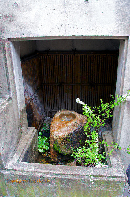 Naramachi, Nara Japan on Flickr.A traditional stone tsukubai on the street outside a house in Naramachi, Nara. The rustic and traditional bamboo fence behind, the white gravel and sparse plantings contrast with the modern concrete alcove into which it is built.  The tsukubai is fed by an out of sight pipe under the alcove above that dribbles water down from above.