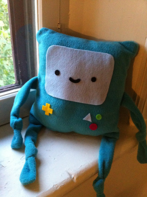 (via BMO pillow preorder by BrendaMakesThings on Etsy) I'm taking pre-orders for the next batch of BMO pillows!  They're soft fleece, and ten by ten inches in size!  The face is made from felt.  During pre-order, they are $15.00.  I will start making the pillows on may 10th!