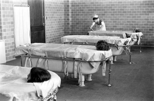 "life:  Unsettling photographs taken inside a psychiatric hospital in 1938. Caption from LIFE. ""Continuous-flow bath is the best method for calming excited mental cases. With their bodies greased, the patients can remain in the baths for hours, gradually fall asleep."" (Alfred Eisenstaedt—Time & Life Pictures/Getty Images)"