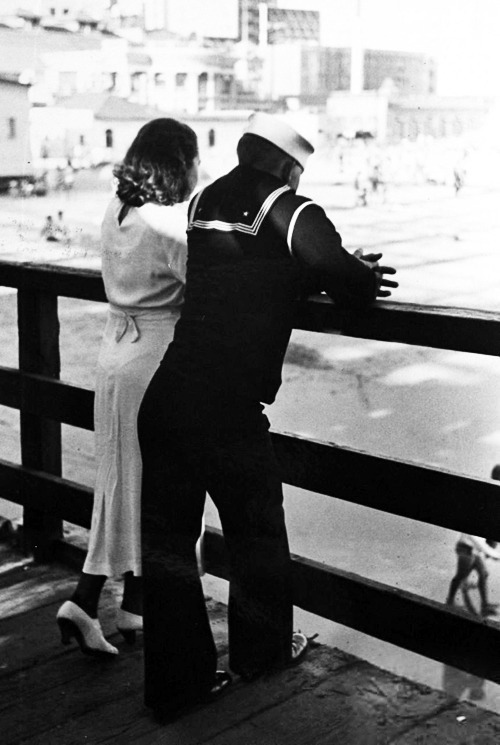 Sailor on shore leave standing on pier with a young woman, 1937 (x)