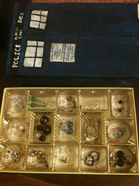 stuckinsidethesnogbox:  TARDIS Jewelry box What You Need: 1 empty chocolate box (I used Whitman's sampler because it's bigger on the inside) White Copy Paper- approximately 4 sheets, but keep extras around just in case Scissors Glue (clear drying is the best) Paint (I used DecoArt Acrylics)- Blue (TARDIS blue), Black, White Paint brushes- one wide Brush, one fine tip Pencil, Black Pen, and black fine tip Sharpie Ruler Estimated Time: 1-2 Hours, less if you're good at these sort of things, more if you are not How to: Take the tray out of the box Completely wrap both the top and the bottom in copy paper, cutting however necessary . Use the glue to stick the paper to the box and to seal the edges of the paper. If you are using the Whitman's box or something similar in design, you don't have to completely wrap the bottom part, just the surface and ledge.  Paint the top and bottom TARDIS blue using the wide brush.  In order to get the watercolor effect on the sides, start by using the wide brush to paint a dark patch of blue. Then dip the brush in water and spread the color along the side in horizontal stripes.  Wait for the paint to dry and add a second coating. If you're impatient, like me, stick it in the microwave for anywhere between 10 and 20 seconds.  Wait for the second coat to dry (or stick it in the microwave again) and start drawing the details (ie the windows and the police box sign) using the pencil and ruler Outline all the pencil lines (such as the squares in the doors) in black sharpie. Paint the windows and the Police Telephone sign white using the fine tip brush. Also, paint the Public Call sign and the bars and outline of the windows black using the fine tip brush.  Write the words Police Box, Public call in pencil on the black strip, and using the back of a paintbrush dipped in white paint, write the words in. Write the POLICE TELEPHONE sign in Black pen and draw door handles in Sharpie Repeat steps six through ten on the other side of the box Wait for the paint to dry, and replace the tray. The TARDIS is now ready to be filled with your jewelry.