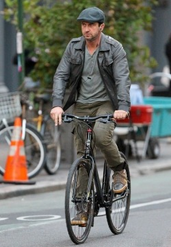 Gerard Butler biking in style with a simple ivy cap.