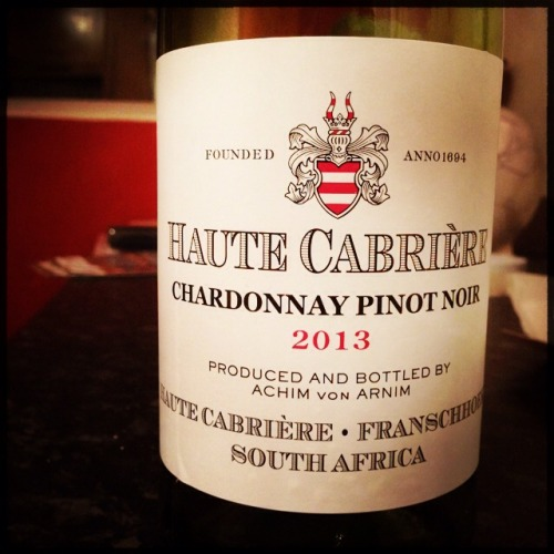 """Haute Cabriere Chardonnay / Pinot Noir 2013 (Franschhoek, South Africa)  I'm convinced that something happens to me when I taste wines at the winery where they've been made, or even worse, when sitting amongst the vines that have produced the grapes themselves. Wines that perhaps might be fairly run of the mill can sometimes seem much better. There you are sitting in the sun, with an incredible view and more often that not chatting with the winemaker themselves. It all adds up to the perfect condition for rose tinted tastebuds….  In November 2012 I found myself (on honeymoon) having a meal at Haute Cabrierre in Franschhoek and trying an earlier vintage of their still Chardonnay / Pinot Noir blend. It's obviously not unusual to find these two grapes combined in a sparkling wine but it's not that often it happens in a still wine. I really enjoyed it but wondered if the meal, the shiny new wife and the incredible views were coming into play.  I've not had the wine since last Friday when I stopped by the Wine Press in Stourbridge. Gone were the rolling mountains and idyllic climate and the wife was no longer new, so would the wine still impress? If ever there were ideal laboratory conditions these were surely them….  Happily, the wine did still impress. Quite a lot actually. I love that it's just a bit different. The wine itself is approaching a rusty colour, it's not quite pink enough to be """"blush"""". On the palate the best bits of Chardonnay express themselves well with a slight creaminess and minerality. Crucially though the Pinot adds a slight sweetness and fruitiness to really give the wine a pleasing finish.    So there you have it, a wine that drinks well on honeymoon or just at home in the West Midlands. How's that for versatility?…..  Available for £10.99 from The Wine Press in Stourbridge, West Midlands."""