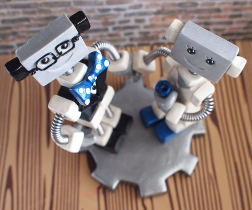 Commission: Robot Wedding Cake Topper Blue and Geeky on Flickr.Custom details requested: square thing robot couple accented in blue, polka dot bow tie, a single flower, holding hands and square framed eye glasses for the groom. Robot sculptures combining polymer clay, wire woven into coil springs, varnish and a little heart handmade by HerArtSheLoves. theawesomerobots.com