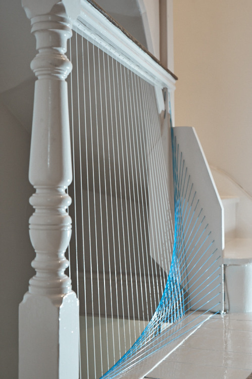 "Leander Angerer and I were commissioned to re-design a Georgian staircase over three stories for a client in North West London.  We decided that instead of embellishing an already beautiful piece of joinery, we could subtract the parts that the client disliked, replacing them when necessary, with elements that would lighten the structure. Tennis racket string sewn into the hand rail replaces the ballusters while a marble plinth replaces the first step and trellis work frame.  Handrails were ""bent"" to remove extraneous parts - opening up the landing areas.  High gloss epoxy floor paint, normally found in factories, creates a continuous pure white ribbon from top floor to bottom. Photography by Colin Ross. 2012/13"