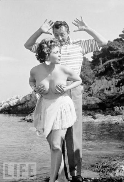 "scottpatrick:  ""Miss Festival"" Simone Silva poses topless with Robert Mitchum during the Cannes Film Festival in April 1954. This pose caused a rush in which one photographer broke his arm and another his leg as the paparazzi scrambled for pictures. Actress Silva was subsequently asked to leave Cannes."