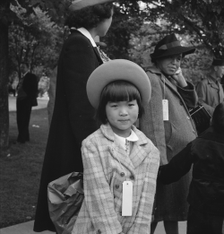 bygoneamericana:  A girl awaiting the evacuation bus with her family. Hayward, California, 1942. By Dorothea Lange