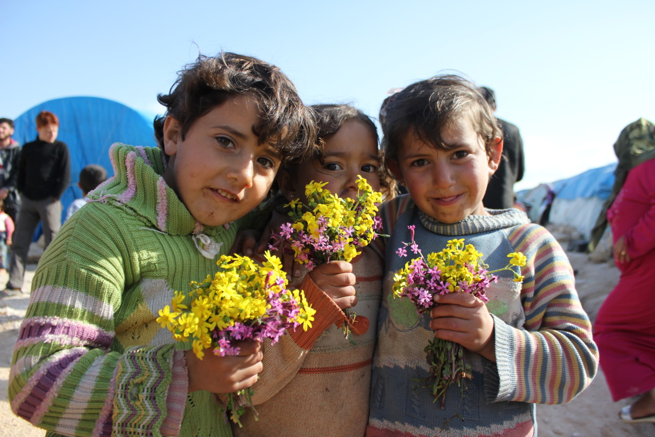 Children pose for a photograph after spending the afternoon picking flowers. Qah Refugee Camp - Syria