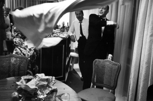 In Miami in 1965, Frank Sinatra tosses a tablecloth after yanking it from a cluttered tabletop.