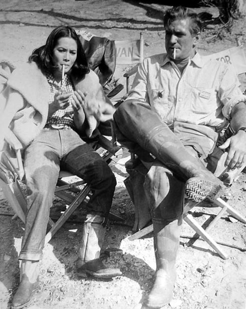 Nancy Kwan and Rod Taylor pause for a cigarette during filming of Fate Is the Hunter, 1964.