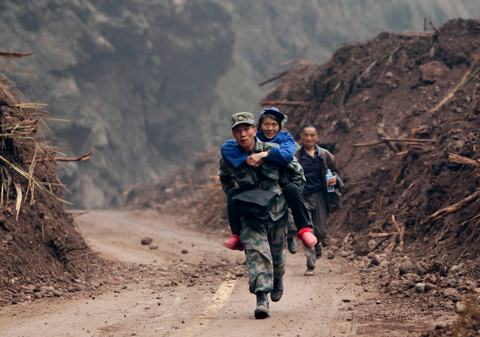 Zhang Bin, a Chinese People's Liberation Army soldier, carries a 60-year-old survivor as he runs down a stretch of the road to Lingguan township which was recently cleared of debris from landslides caused by Saturday's earthquake, in Baoxing county in Ya'an, Sichuan province April 22, 2013. REUTERS/Jason Lee